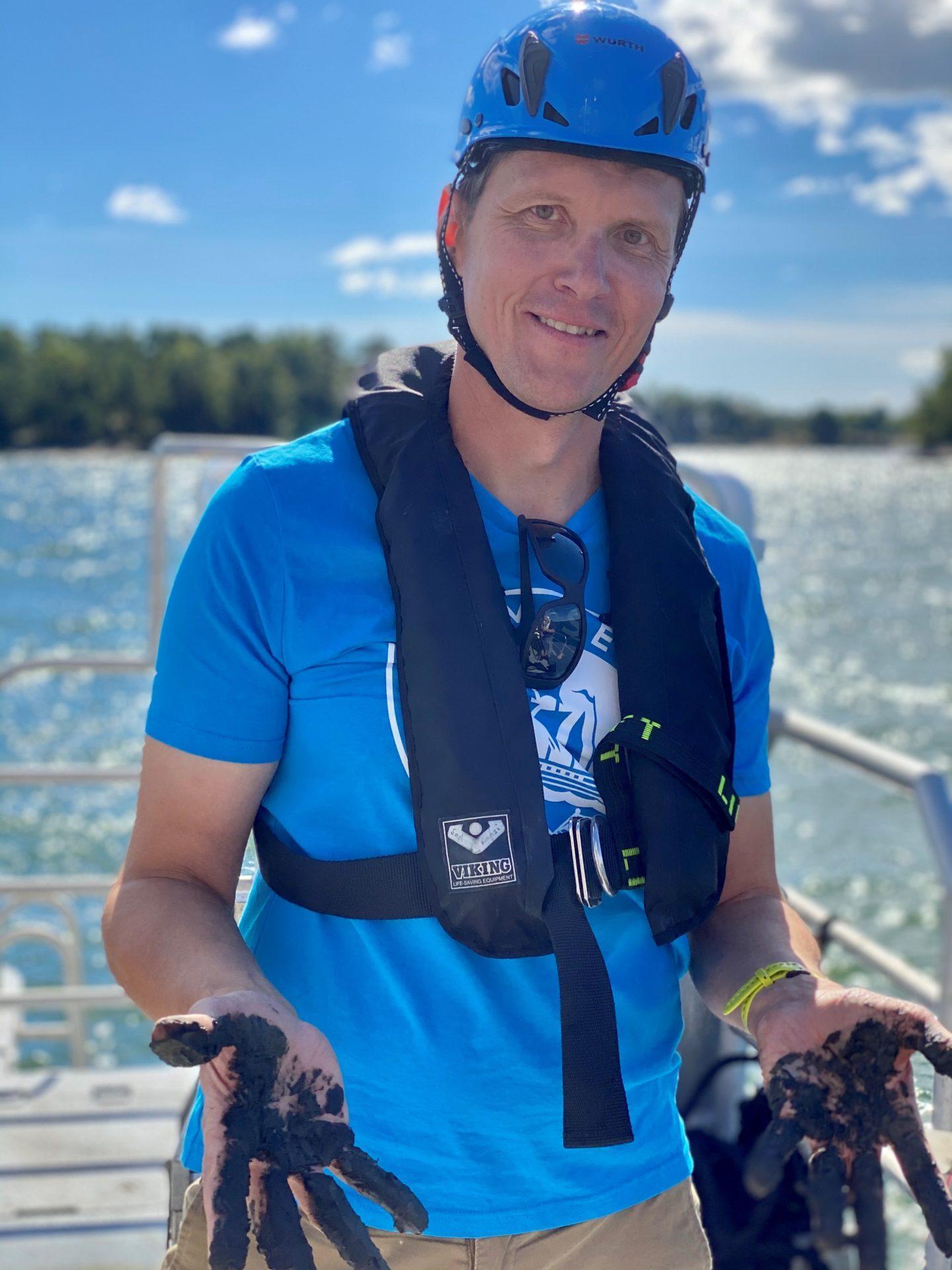 Tommi Juusela Itämeripäivänä Tvärminnessä R/V Augustalla. Käsissä pohjasedimenttiä. Kuva: Alf Norkko.