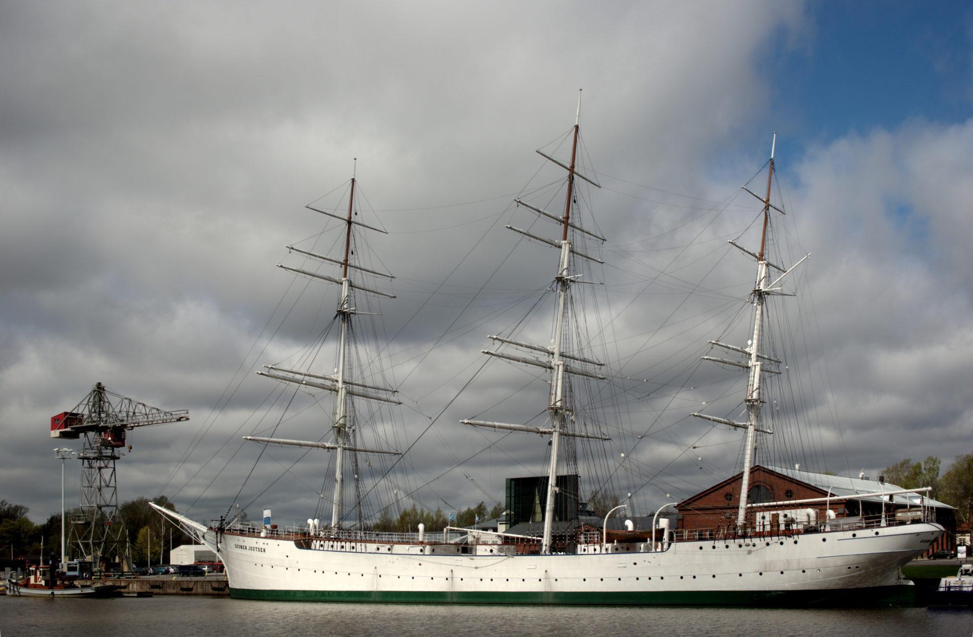 Suomen Joutsen-laiva Aurajoen rannalla Turussa pilvisenä päivänä